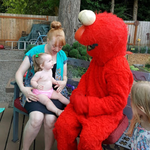 Elmo party character from Blast Kids' Parties with a young party guest.